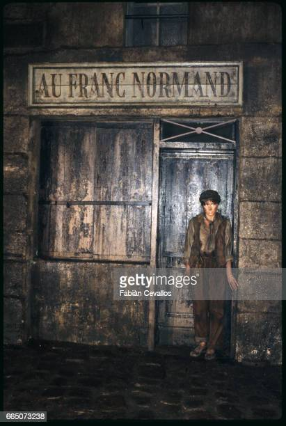 Young French actress Candice Patou as Eponine stands in front of a store named Au Franc Normand in a scene taken from the 1982 movie Les Miserables...