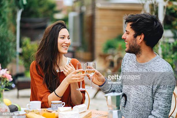 Young French couple having a brunch in the garden