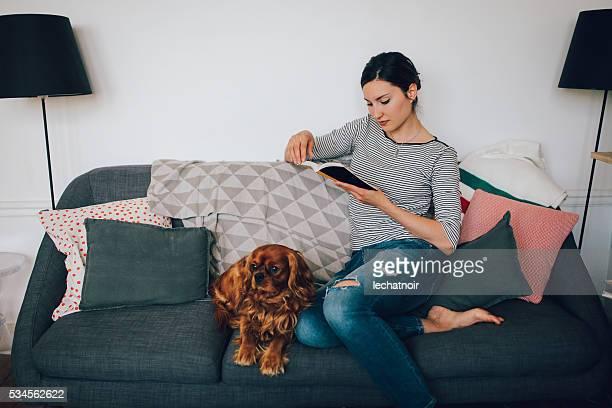 若いフレンチくつろいでいる女性ソファー本を読んでいる