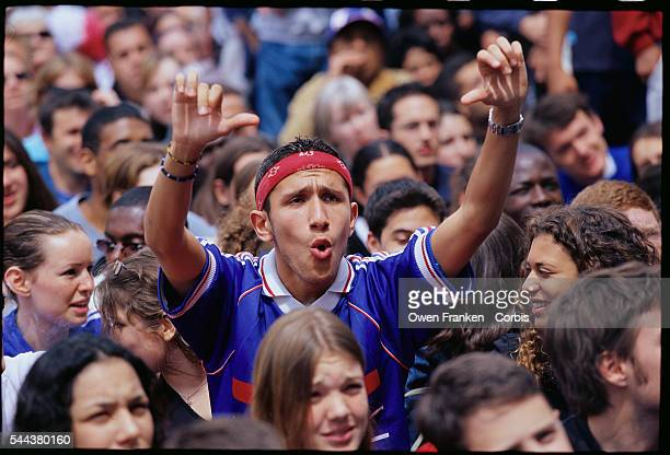 A young Frenchman boos and gives the 'thumbs down' sign while he watches Denmark defeat France in the 2002 World Cup The game is broadcast live to...