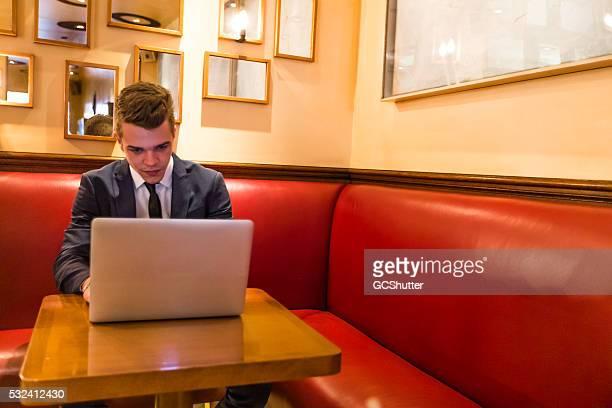 Junge Franzose arbeiten mit seinem Laptop in einem Café