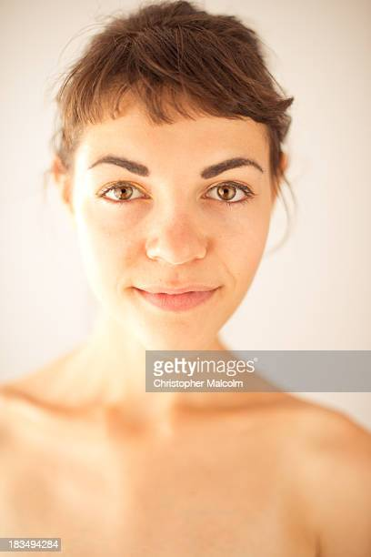 Young fresh faced girl smiles at camera