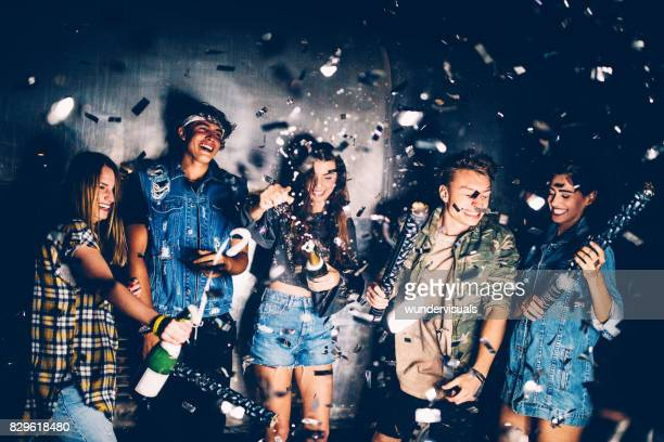 Young friends celebrating with champagnes and confetti at party