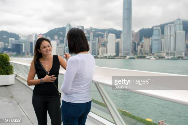 Young friends chatting with Hong Kong skyline backdrop