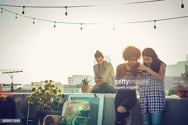 Young friends checking smartphones on urban roofto