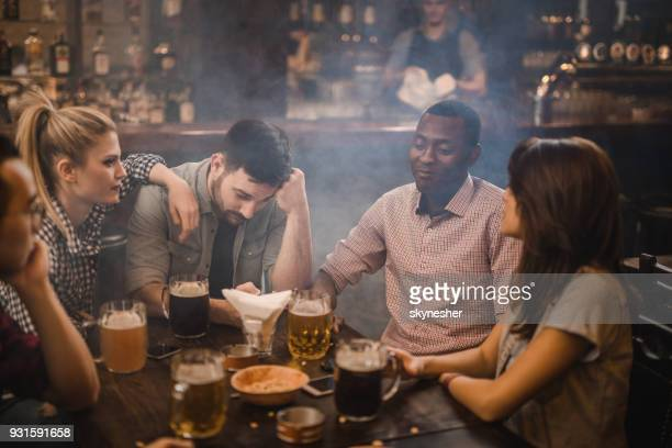 young friends communicating while sitting at the table in a bar. - good; times bad times stock pictures, royalty-free photos & images