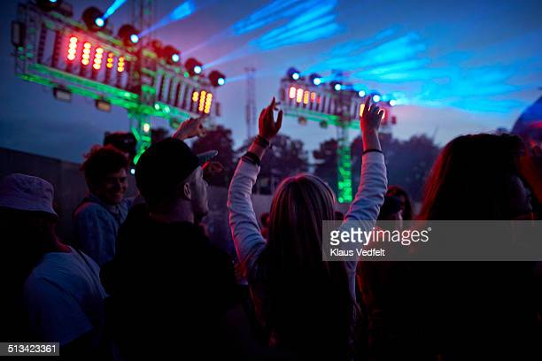 Young friends dancing at concert at night