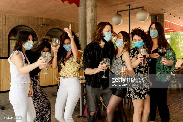 young friends dancing while holding drinks at restaurant during coronavirus - party imagens e fotografias de stock