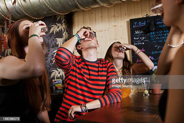 young friends drinking from shot glass in bar - visual_effects stock pictures, royalty-free photos & images