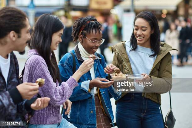 young friends enjoying street food in tokyo - takoyaki stock pictures, royalty-free photos & images