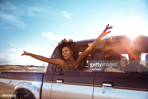 young friends enjoying the freedom on a car trip over a country offroad - carefree stock pictures, royalty-free photos & images