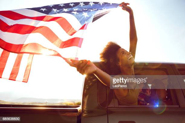 young friends enjoying the freedom on a car trip over a country offroad - patriotic stock pictures, royalty-free photos & images