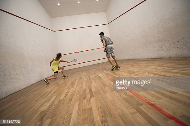Young friends exercising squash on a court.