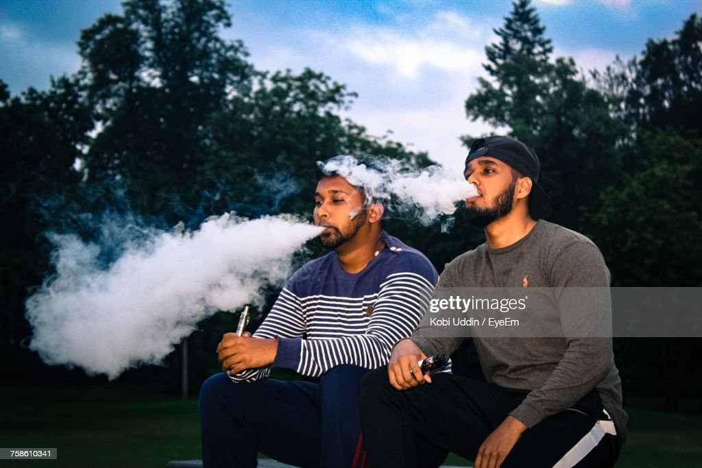 Young Friends Exhaling Smoke While Sitting At Park During Sunset : Stock Photo