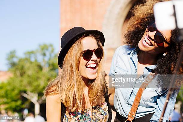 Young friends fooling with smartphone and taking a selfie.