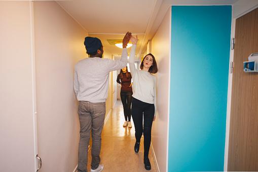 Young friends giving high-five walking in corridor of college dorm - gettyimageskorea