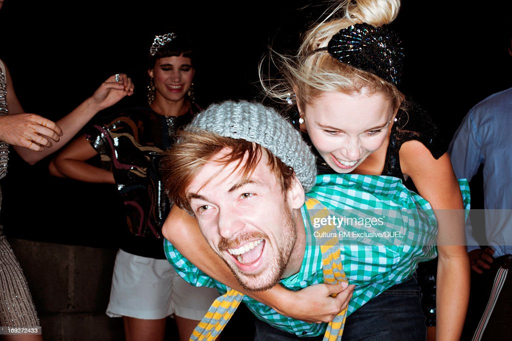 Young friends giving piggybacks at party : Stock Photo