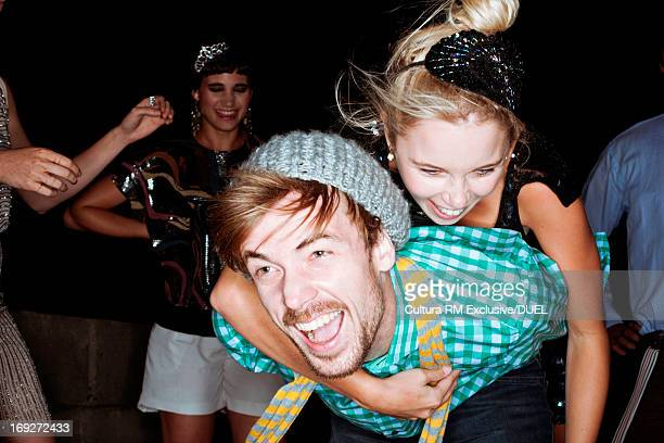 young friends giving piggybacks at party - freaky couples stock photos and pictures