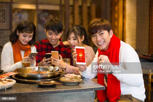 Young friends grabbing Wechat hongbao with smart phones