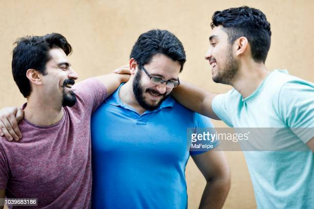 young friends happily hugging each other at a party - fat man beard stock photos and pictures