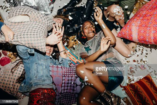 young friends having a pillow fight with confetti floating about - house after party stock pictures, royalty-free photos & images