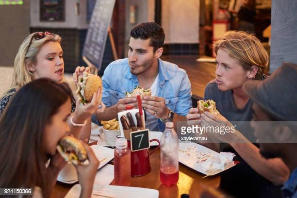 Young friends having burgers in restaurant