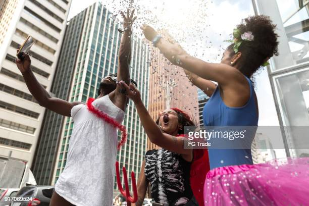 young friends having carnival party at the street - carnival celebration event stock pictures, royalty-free photos & images