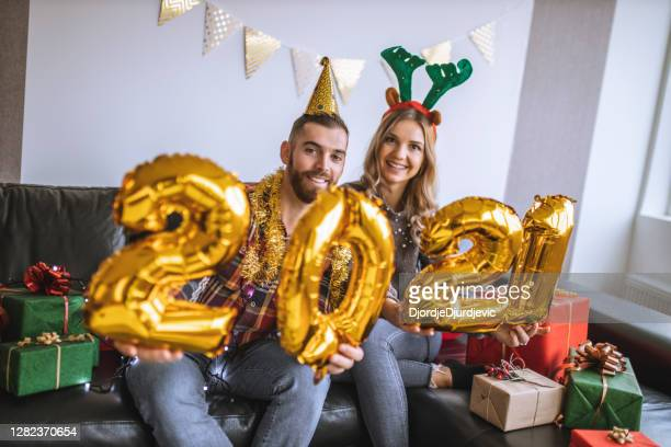 young friends having fun at new years party, holding balloon numbers 2021 representing the upcoming new year - 25 29 years stock pictures, royalty-free photos & images