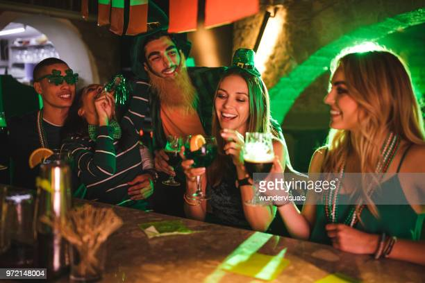young friends having fun at saint patrick's day bar party - st patricks day stock pictures, royalty-free photos & images