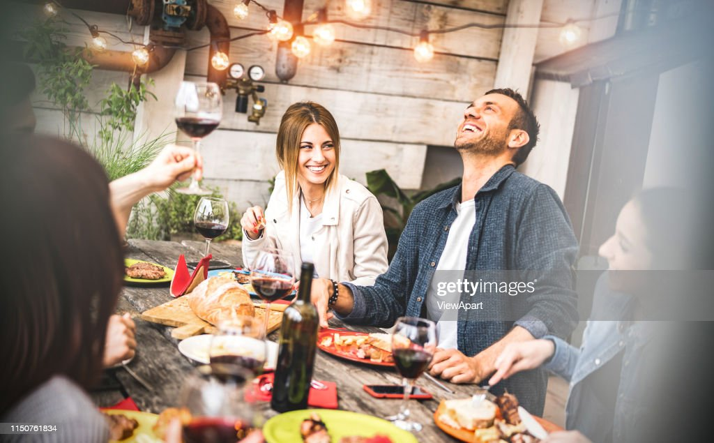 Young friends having fun drinking red wine on balcony at house dinner party - Happy people eating bbq food at fancy alternative restaurant together - Dining lifestyle concept on desaturated filter : Stock Photo