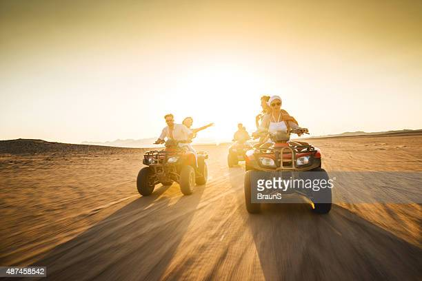 Young friends having fun on quad bikes at sunset.
