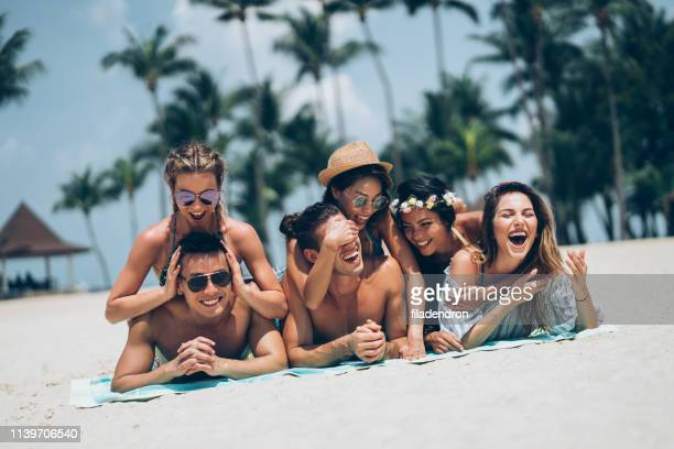 young friends having fun on the beach - medium group of people stock pictures, royalty-free photos & images