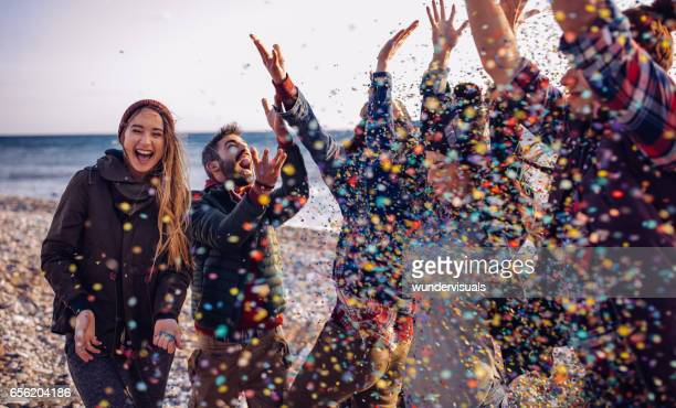 Young friends having fun throwing confetti on a beach