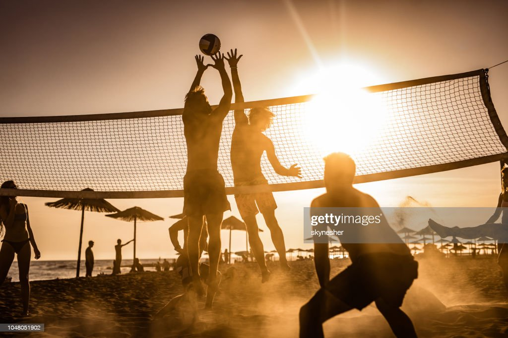 Young friends having fun while playing beach volleyball at sunset. : Stock Photo