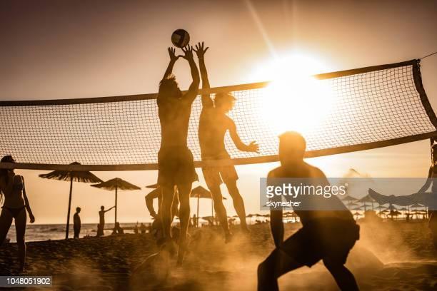 junge freunde, die spaß beim spielen beach-volleyball bei sonnenuntergang. - strand volleyball stock-fotos und bilder
