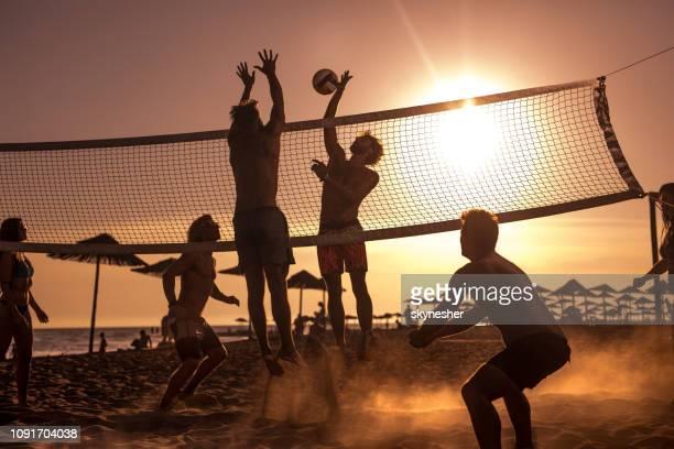 junge freunde, die spaß beim spielen beach-volleyball bei sonnenuntergang. - strandvolleyball spielerin stock-fotos und bilder
