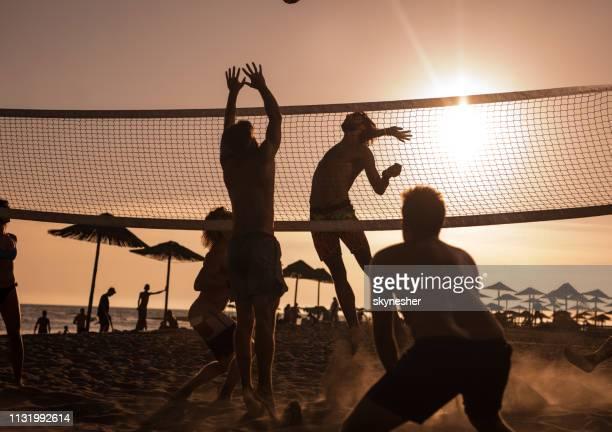 junge freunde haben spaß beim beachvolleyball bei sonnenuntergang. - strand volleyball stock-fotos und bilder