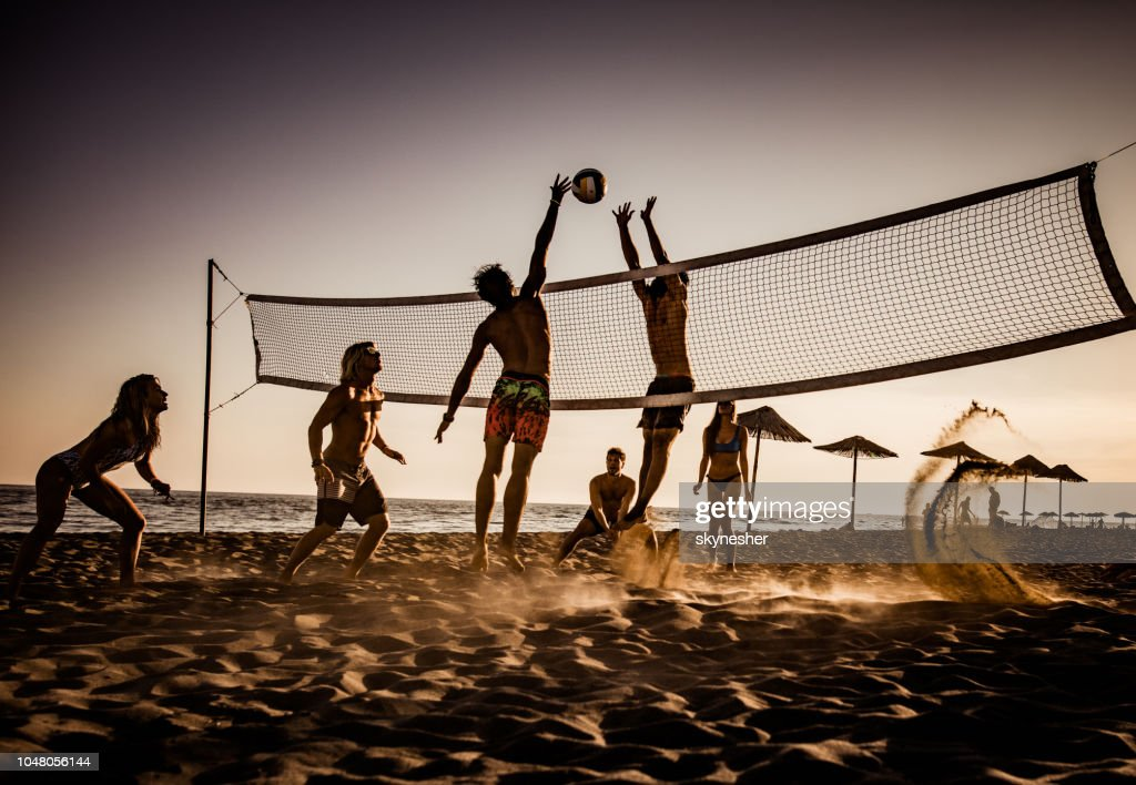 Young friends having fun while playing volleyball on the beach. : Stock Photo