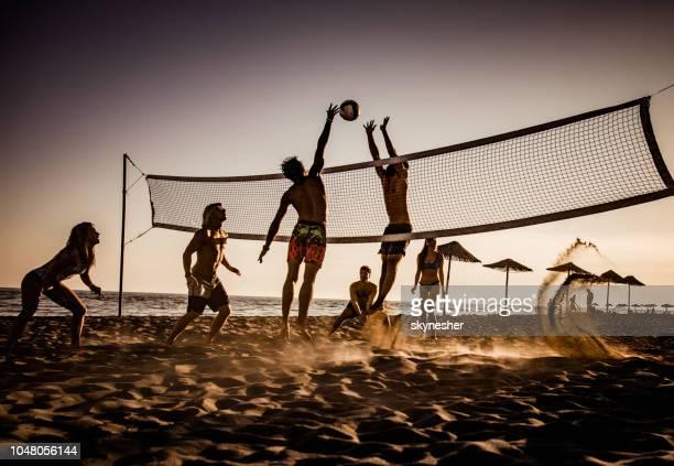 junge freunde, die spaß beim volleyball am strand spielen. - strand volleyball stock-fotos und bilder