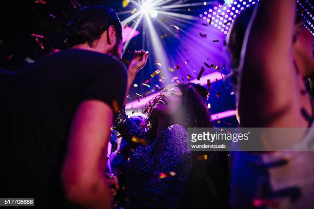 young friends having fun with confetti on night club party - dancing stockfoto's en -beelden