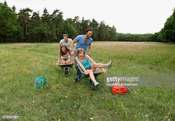 Young friends having race on wheelbarrow