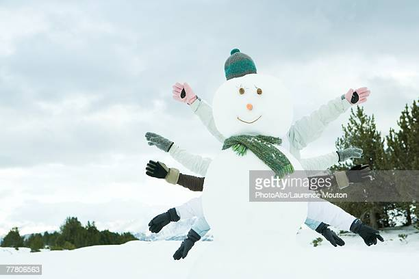 Young friends hiding behind snowman, arms outstretched