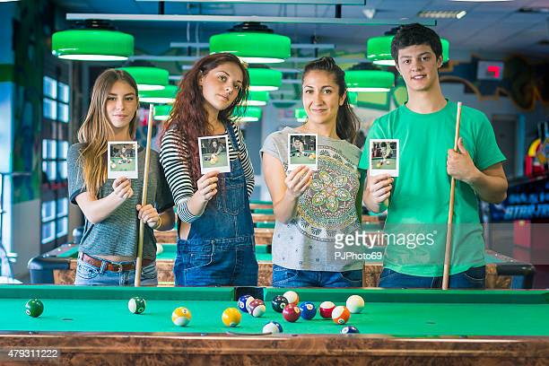 Young friends in a billiard-room holding photos