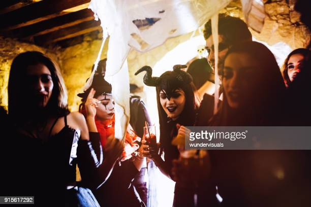 young friends in halloween costumes dancing and drinking at party - halloween party stock photos and pictures