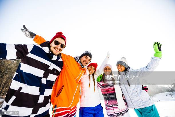Young friends in ski-wear with arms raised