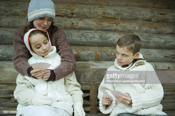 young friends in winter clothes playing cards - knit hat stock pictures, royalty-free photos & images