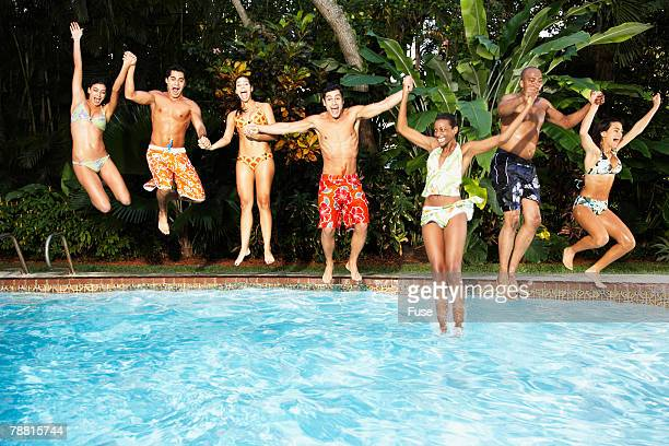 Young Friends Jumping in to Swimming Pool