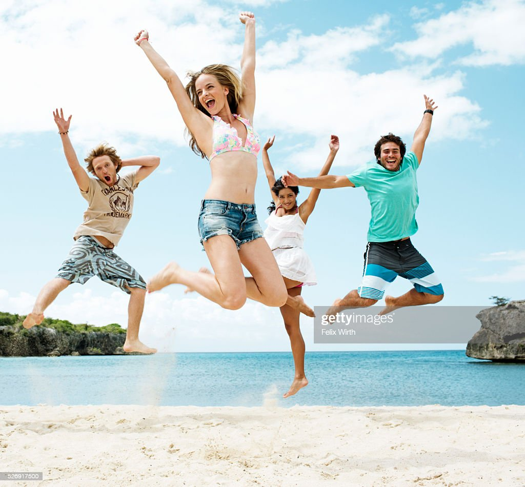 Young friends jumping on beach : Foto de stock