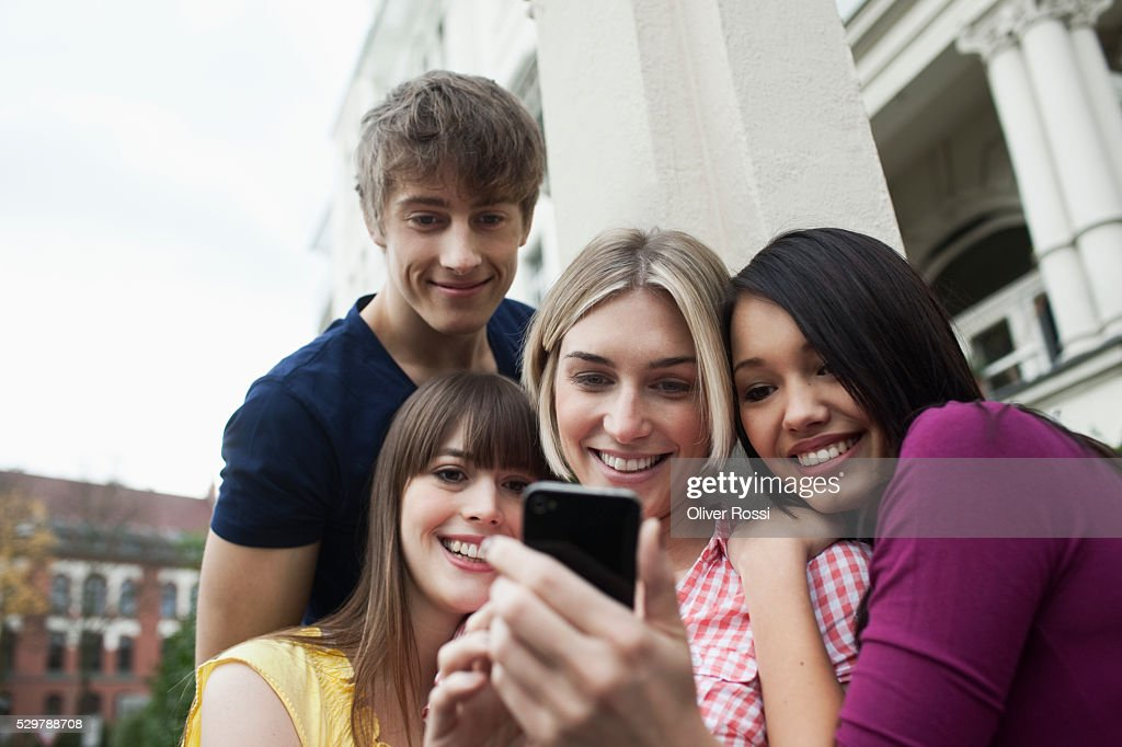 Young friends looking at a picture : Stock Photo