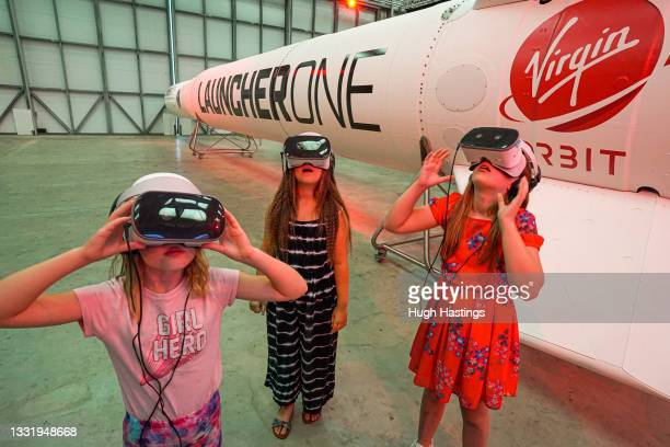 Young friends Lottie, Lilly and Tiggy use VR units in front of the Virgin Orbit Launcher One rocket on the opening day of the Story of a Satellite...